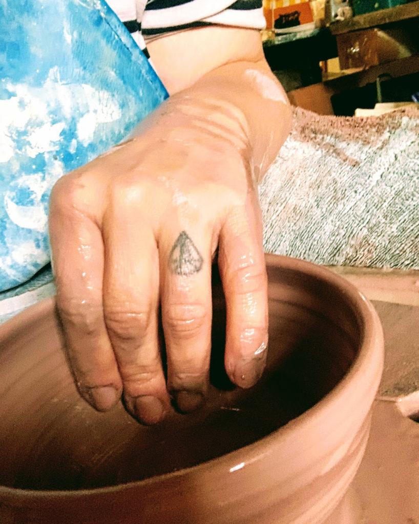 Hand throwing clay pot on wheel.